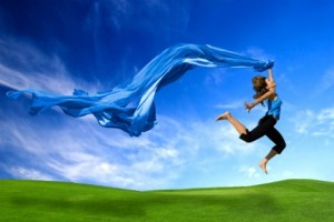 Beautiful athletic woman jumping on a green meadow with a scarf